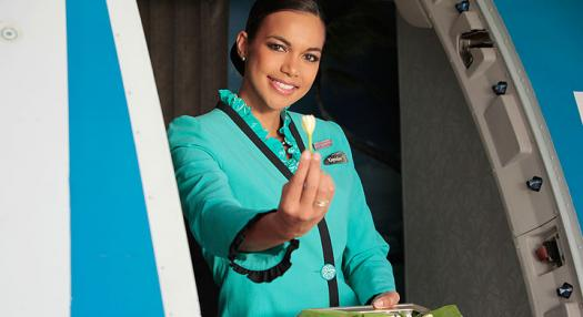 Photo of a a hostess offering a Tiare flower at the entrance of the Air Tahiti Nui plane