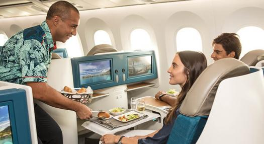 Air Tahiti Nui flight attendant servicing Poerava Business class