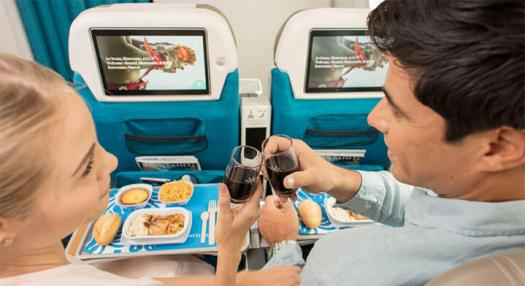 Couple enjoying service and entertainment aboard Air Tahiti Nui Dreamliner
