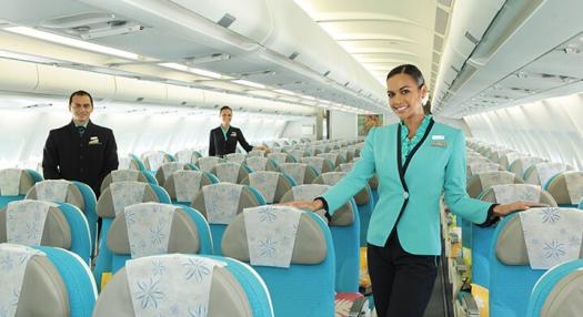 Flight attendant waiting for passengers in Air Tahiti Nui economy class