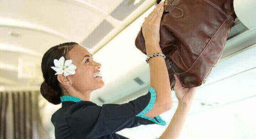 Photo of a hostess that places a bag into the overhead lockers