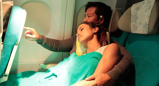 A couple relaxing and using in flight entertainment in the Moana economic class of Air Tahiti Nui