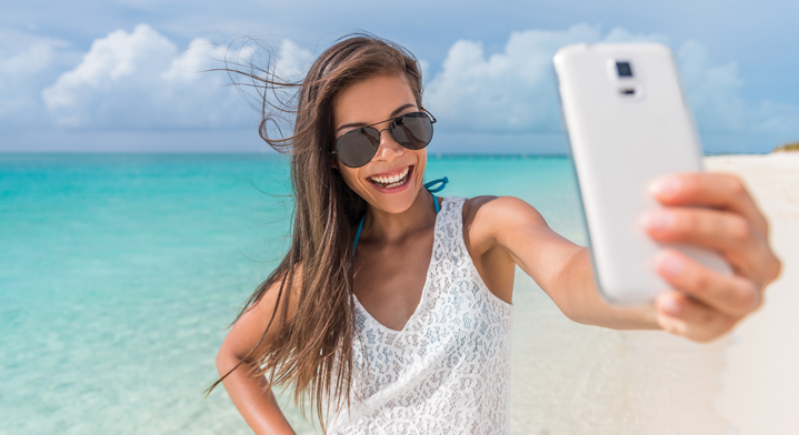 woman smiling on the tahiti beach and doing a selfie